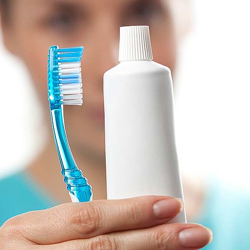 Woman holding a toothbrush and toothpaste in her hand